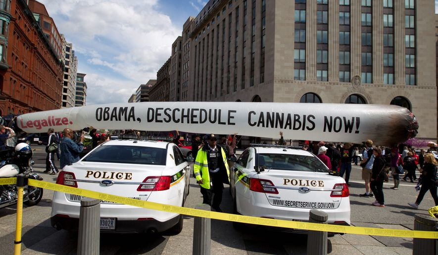 Demonstrators carry a 51-foot inflatable joint as they march for the legalization of marijuana outside of the White House on Saturday, where they demanded President Obama stop marijuana arrests and pardon offenders. (Associated Press)