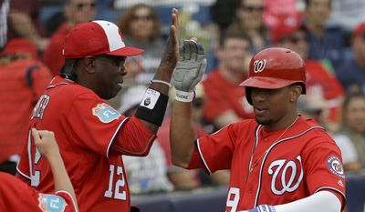 Washington Nationals manager Dusty Baker, left, high fives Ben Revere, right, after he hit a home run in a spring training baseball game against the Detroit Tigers, Saturday, March 5, 2016, in Viera, Fla. (AP Photo/John Raoux)