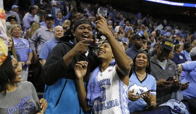 FILE - I this Sunday, March 27, 2016, file photo, North Carolina's Nate Britt, right, and Villanova's Kris Jenkins celebrate after North Carolina won a regional final men's college basketball game against Notre Dame in the NCAA Tournament in Philadelphia. North Carolina won 88-74 to advance to the Final Four. Jenkins and Britt, brothers in every way except blood, are giving each other the silent treatment for about 48 hours. (AP Photo/Matt Rourke, File)