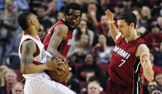 Miami Heat forward Amare Stoudemire reaches in on Portland Trail Blazers guard Damian Lillard as Heat guard Goran Dragic (7) defends during the first quarter of an NBA basketball game in Portland, Ore., Saturday April 2, 2016. (AP Photo/Steve Dykes)