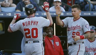 Washington Nationals' Daniel Murphy (20) is met at the dugout by catcher Jose Lobaton (59) after hitting a home run in the fourth inning of a baseball game against the Atlanta Braves, Monday, April 4, 2016, in Atlanta. (AP Photo/John Bazemore)