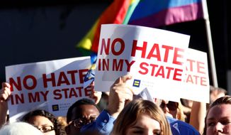 Protesters call for Mississippi Gov. Phil Bryant to veto House Bill 1523, which they say allows discrimination against LGBT people, during a rally on Monday. (Associated press)