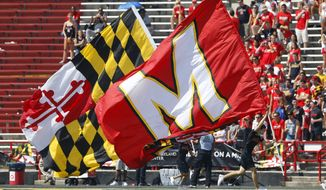 Maryland cheerleaders carry flags in the first half of an NCAA college football game against South Florida, Saturday, Sept. 19, 2015, in College Park, Md. (AP Photo/Patrick Semansky)