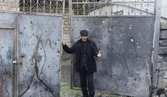 Elmar Abdullayev, 55, stands at a gates of his home hit by shelling in a village of Gapinli, in Terter region of Azerbaijan on Tuesday, April 5, 2016. Azerbaijan and separatist forces in Nagorno-Karabakhk on Tuesday agreed on a cease-fire starting noon local time following three days of the heaviest fighting in the disputed region since 1994, the Azeri defense ministry announced. Gapanli, a village south of Terter, has been one of the hardest hit. Houses bear the marks of the recent shelling; metal doors are riddled with shrapnel, power lines are cut down, craters are seen in the yards. (AP Photo/ Hicran Babayev)