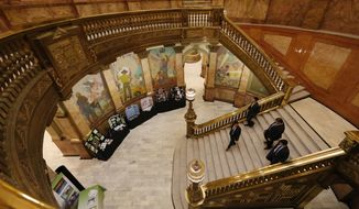 A group of men head down the central staircase in the Colorado State Capitol, Tuesday, April 5, 2016, as lawmakers meet in session. (AP Photo/David Zalubowski) ** FILE **