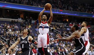 Washington Wizards guard Ramon Sessions (7) shoots between Brooklyn Nets guards Shane Larkin (0) and Rondae Hollis-Jefferson (24) during the first half of an NBA basketball game Wednesday, April 6, 2016, in Washington. (AP Photo/Alex Brandon)