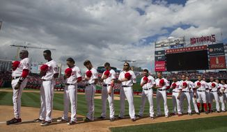 The Washington Nationals line up for the national anthem before their first home game against the Miami Marlins, at Nationals Park, on Thursday. (AP Photo/Evan Vucci)