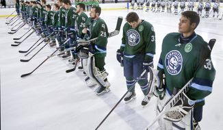 In this Feb. 6, 2016 photo provided by Connecticut College, the men's hockey team lines for a game against Tufts, wearing a special patch to mark the fifth annual Green Dot hockey game, on the campus in New London, Conn. The U.S. Air Force visited the college in March to get an up-close look at a school that has been using the Green Dot program to stem sexual assault, a problem that has been the target of crackdowns in recent years in higher education and the armed forces. The Air Force is introducing the program at all installations across the service. (Bob McDonnell/Connecticut College via AP) MANDATORY CREDIT