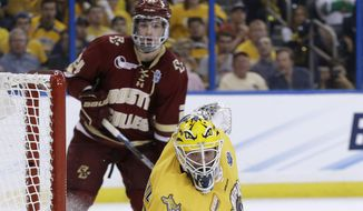 Quinnipiac goalie Michael Garteig (34) makes a pad save on a shot by Boston College during the third period of an NCAA Frozen Four men's college hockey semifinal, Thursday, April 7, 2016, in Tampa, Fla. Looking for a rebound is forward Zach Sanford (24). (AP Photo/Chris O'Meara) ** FILE **