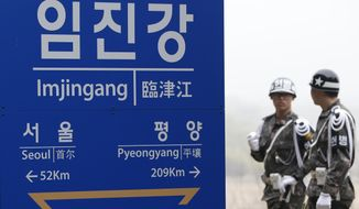 South Korean soldiers walk by a signboard showing the distance to the North Korea's capital Pyongyang and to South Korea's capital Seoul from Imjingang Station near the border village of the Panmunjom in Paju, South Korea, Saturday, April 9, 2016. (AP Photo/Lee Jin-man)