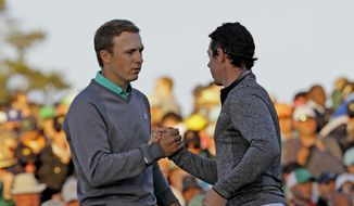 Jordan Spieth, left, shakes hands with Rory McIlroy, of Northern Ireland, on the 18th green during the third round of the Masters golf tournament Saturday, April 9, 2016, in Augusta, Ga. (AP Photo/David J. Phillip)