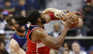 Washington Wizards center Nene, right, from Brazil, is fouled by Charlotte Hornets forward Spencer Hawes during the first half of an NBA basketball game Sunday, April 10, 2016, in Washington. (AP Photo/Alex Brandon)