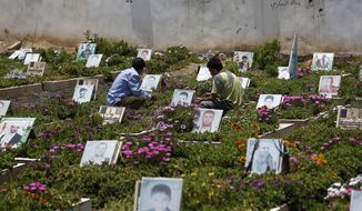 Shiite rebels, known as Houthis, pray at portrait adorned graves of Houthi fighters and supporters who were killed in the ongoing conflict in Yemen, a few hours before the start of a fresh cease-fire in Sanaa, Yemen, Sunday, April 10, 2016. (AP Photo/Hani Mohammed)