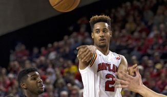 Maryland's Melo Trimble (2) passes the ball as Princeton's Amir Bell (5) tries to block during the second half of an NCAA college basketball game at Royal Farms Arena in Baltimore, Saturday, Dec. 19, 2015. (AP Photo/Jose Luis Magana)