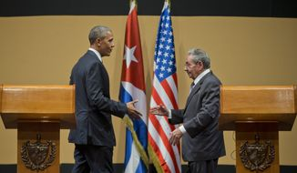 President Barack Obama with Cuban President Raul Castro prepare to shake hands at their joint news conference at the Palace of the Revolution, Monday, March 21, in Havana, Cuba. (AP Photo/Pablo Martinez Monsivais)