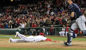Washington Nationals' Anthony Rendon slides safely home to score on a two-run double by Bryce Harper as Atlanta Braves catcher Tyler Flowers holds the ball during the eighth inning of a baseball game at Nationals Park, Tuesday, April 12, 2016, in Washington. The Nationals won 2-1. (AP Photo/Alex Brandon)