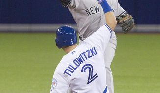 Toronto Blue Jays' Troy Tulowitzki is out on the force out at second base as New York Yankees' Didi Gregorius turns the double play on Chris Colabello during the third inning of a baseball game Tuesday, April 12, 2016, in Toronto. (Fred Thornhill/The Canadian Press via AP)