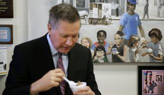 A painting depicting children eating ice cream is seen behind Republican presidential candidate, Ohio Gov. John Kasich as he eats chocolate ice cream during a visit to You Scream Ice Cream in Catonsville, Md., Wednesday, April 13, 2016. (AP Photo/Patrick Semansky)