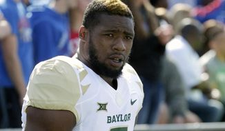 FILE - In this Oct. 10, 2015, file photo, then-Baylor defensive end Shawn Oakman warms up before an NCAA college football game against Kansas in Lawrence, Kan. NFL prospect and former Baylor football player Oakman was arrested Wednesday, April 13, 2016, on a charge of sexually assaulting a woman at his Texas apartment earlier this month, Waco police said Wednesday. (AP Photo/Charlie Riedel, File)
