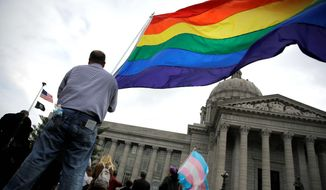 Protesters wave flags on March 24 outside the North Carolina Executive Mansion in Raleigh, N.C. North Carolina passed a law that bans cities and counties from passing anti-discrimination ordinances. (Associated Press)