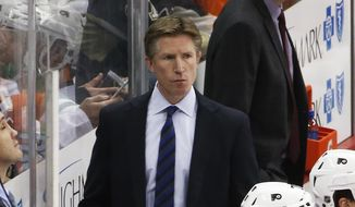 Philadelphia Flyers head coach Dave Hakstol, center, stands behind his bench during an NHL hockey game against the Pittsburgh Penguins in Pittsburgh, Thursday, Jan. 21, 2016. (AP Photo/Gene J. Puskar)