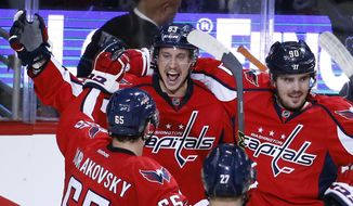 Washington Capitals center Jay Beagle (83) celebrates his goal with left wing Andre Burakovsky (65), from Austria, defenseman Karl Alzner (27) and center Marcus Johansson (90), from Sweden, during the third period of Game 1 of a first-round NHL hockey Stanley Cup playoff series against the Philadelphia Flyers, Thursday, April 14, 2016, in Washington. The Capitals won 2-0. (AP Photo/Alex Brandon)
