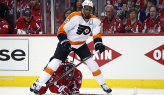 Philadelphia Flyers right wing Wayne Simmonds (17) skates over Washington Capitals center Evgeny Kuznetsov (92), from Russia, during the second period of Game 1 in the first round of the NHL Stanley Cup hockey playoffs, Thursday, April 14, 2016, in Washington. (AP Photo/Alex Brandon)