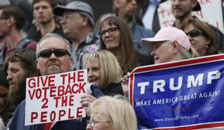 Darrin Black, left, of Thornton, Colo., holds up a placard as he joins supporters of the Republican presidential candidate Donald Trump to demonstrate on the steps of the Colorado State Capitol Friday, April 15, 2016, in downtown Denver. Colorado supporters of Trump were protesting the convoluted procedure that led Ted Cruz to sweep all the state's 34 delegates to the national convention during the state Republican assembly last weekend in Colorado Springs, Colo. (AP Photo/David Zalubowski)