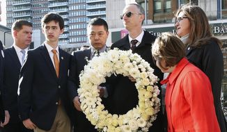 Family members of Boston Marathon bombing victim Martin Richard, Bill, third from right, Denise, right, Jane, second from right, and Henry, second from left, along with the father of victim Lingzi Lu, Jun Lu, third from left, and Boston Mayor Marty Walsh, left, prepare to place a wreath on the third anniversary of the bombings, Friday, April 15, 2015, in Boston. (AP Photo/Michael Dwyer)