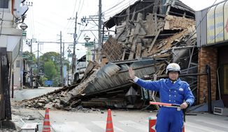 A police officer stands guard in front of a house destroyed by an earthquake in Mashiki, Kumamoto prefecture, southern Japan Saturday, April 16, 2016. A powerful earthquake struck southern Japan early Saturday, barely 24 hours after a smaller quake hit the same region. (Ryosuke Uematsu/Kyodo News via AP)
