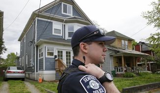 Seattle Police officer Scott LaPierre stands in front of a house, Friday, April 15, 2016, after human remains were found in a container by a sanitation worker in front of the house in Seattle. Seattle Assistant Police Chief Robert Merner said authorities were investigating the probable connection between the remains found Friday and the recent murder of Ingrid Lyne, whose partial remains were found in a recycling bin earlier in the week. (AP Photo/Ted S. Warren)