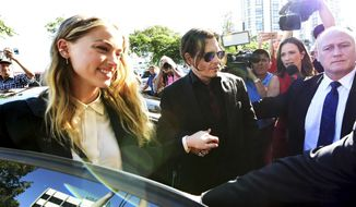 Johnny Depp, center, and wife Amber Heard, left, arrive at the Southport Magistrates Court on the Gold Coast, Australia, Monday, April 18, 2016. Heard pleaded guilty to providing a false immigration document amid allegations she smuggled the couple's dogs into Australia. (Dave Hunt/AAP Image via AP)