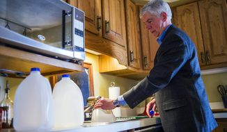 Michigan Gov. Rick Snyder fills jugs with filtered Flint, Mich., tap water at Cheryl Hill's house Monday, April 18, 2016, on the city's east side. (Jake May/The Flint Journal-MLive.com via AP) ** FILE **