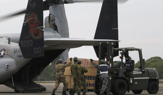 Japan's Ground Self Defense Force and U.S. military members load relief goods onto MV-22 Osprey which arrived in their Takayubaru vice camp in earthquake-hit Mashiki, Kumamoto prefecture, southern Japan, Monday, April 18, 2016. U.S. airlifts were delivering water, bread, ready-to-eat food and other emergency supplies Monday to a remote area of southern Japan stricken by two powerful earthquakes, as local rescuers searched for 10 people still reported missing. (AP Photo/Koji Ueda)
