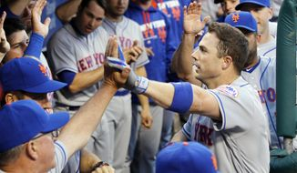 New York Mets' David Wright returns to high fives in the dugout after his solo homerun during the first inning of a baseball game against the Philadelphia Phillies Monday, April 18, 2016 in Philadelphia. (AP Photo/Tom Mihalek)