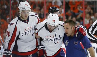 Washington Capitals' Brooks Orpik (44) is helped off the ice after an injury during the second period of Game 3 in the first round of the NHL Stanley Cup hockey playoffs against the Philadelphia Flyers, Monday, April 18, 2016, in Philadelphia. (AP Photo/Matt Slocum)