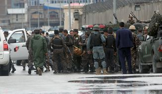 Afghan security forces carry a body at the site of a deadly Taliban-claimed suicide attack in Kabul, Afghanistan, Tuesday, April 19, 2016. Armed militants in Afghanistan have staged a coordinated assault on a key government security agency in the capital Tuesday morning, killing dozens and wounding more than 320 people. (AP Photo/Massoud Hossaini)