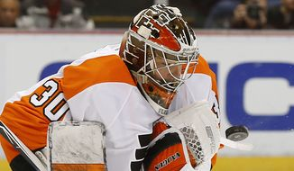 Philadelphia Flyers goalie Michal Neuvirth (30) stops a Detroit Red Wings shot in the second period of an NHL hockey game, Sunday, Jan. 17, 2016 in Detroit. (AP Photo/Paul Sancya)