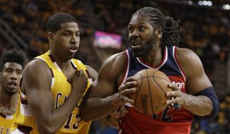 Washington Wizards' Nene Hilario (42), from Brazil, drives past Cleveland Cavaliers' Tristan Thompson (13) in the first half of an NBA basketball game Friday, March 4, 2016, in Cleveland. (AP Photo/Tony Dejak)