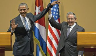 FILE - In this Monday, March 21, 2016, file photo, Cuban President Raul Castro, right, lifts up the arm of President Barack Obama at the conclusion of their joint news conference at the Palace of the Revolution in Havana, Cuba. One of Cuba's most renowned advocates of economic reform has been fired from his University of Havana think tank, on Wednesday, April 20, for sharing information with Americans without authorization, among other alleged violations.(AP Photo/Ramon Espinosa, File)