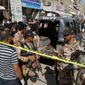 Soldiers of a Pakistani para military force cordon off the area and police vehicle, attacked by gunmen in Karachi, Pakistan, Wednesday, April 20, 2016. The slain police officers had been deployed to protect health workers administering polio vaccinations. No health workers were harmed in the attacks in Karachi, local police official Mohammad Ijaz said. (AP Photo/Fareed Khan)