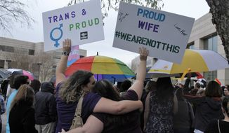 Two protesters hold up signs against passage of legislation in North Carolina, which limits the bathroom options for transgender people, during a rally in Charlotte, N.C., Thursday, March 31, 2016. The rally drew around 100 people at the Charlotte-Mecklenburg Government Center. (AP Photos/Skip Foreman)