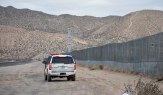 In this Jan. 4, 2016, file photo, a U.S. Border Patrol agent drives near the U.S.-Mexico border fence in Sunland Park, N.M. (AP Photo/Russell Contreras, File)