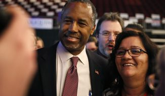 Former Republican presidential candidate Dr. Ben Carson poses with Maine delegates at the state GOP Convention, Friday, April 22, 2016, in Bangor, Maine.  Carson is scheduled to speak to the convention on Friday evening.  (AP Photo/Robert F. Bukaty)
