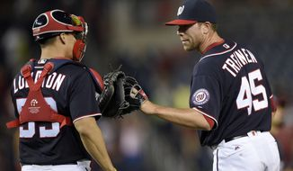 Washington Nationals relief pitcher Blake Treinen (45) celebrates with catcher Jose Lobaton (59) after the Nationals defeated the Minnesota Twins 8-4 in a baseball game Friday, April 22, 2016, in Washington. (AP Photo/Nick Wass)