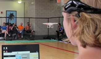 In this April 16, 2016, photo, a University of Florida student uses a brain-controlled interface headset to fly a drone during a mind-controlled drone race in Gainesville, Fla. (AP Photo/ Jason Dearen)