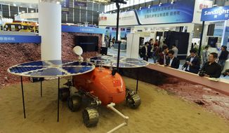 FILE - In thi Nov. 4, 2014, file photo, visitors to the 16th China International Industry Fair (CIIF) look at a prototype of what a Chinese Mars rover would look like in Shanghai, China. Head of the China National Space Administration Xu Dazhe said Friday, April 22, 2016 at a rare news conference that plans are being drawn up for the project that was formally announced in January and that it has the government's full support. (Chinatopix Via AP, File) CHINA OUT