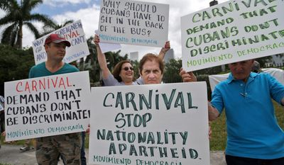 In this April 12, 2016 photo, Victor Garcia, of Miami, from left, Maria Hernandez and Miriam Dominguez, protest against Carnival Corporation as they hold a rally in Doral, Fla. Two Cuban-American men are asking a Miami federal judge to guarantee they and other Cuban exiles will not suffer discrimination on upcoming Carnival Corp. cruises to Cuba. A hearing was held in Miami, Thursday, April 21, 2016. (Carl Juste/The Miami Herald via AP, File)  MAGS OUT; MANDATORY CREDIT