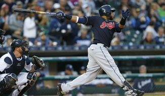 Cleveland Indians' Carlos Santana, right, hits a double against the Detroit Tigers in the first inning of a baseball game, Friday, April 22, 2016, in Detroit. (AP Photo/Paul Sancya)