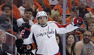 Washington Capitals' Matt Niskanen, right, checks Philadelphia Flyers' Matt Read into the boards during the second period of Game 6 in the first round of the NHL Stanley Cup hockey playoffs, Sunday, April 24, 2016, in Philadelphia. (AP Photo/Matt Slocum)
